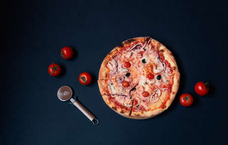 Delicious seafood pizza, pizza cutter and fresh tomatoes on dark background. Top view, copy space. Standard-Bild