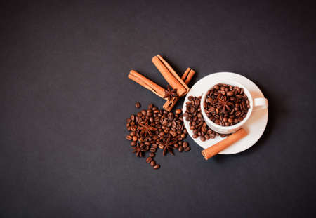 Coffee cup with roasted coffee beans and spices on dark background. Top view with copy space. Standard-Bild