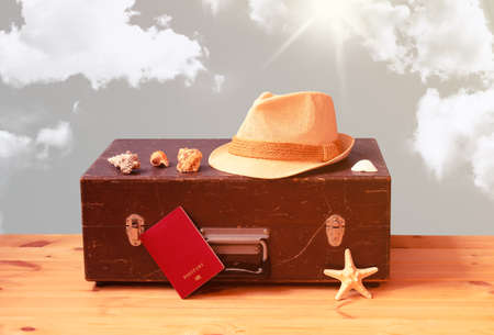Vintage wooden suitcase, hat, passport, starfish and  seashells. Summer holidays and travel concept.