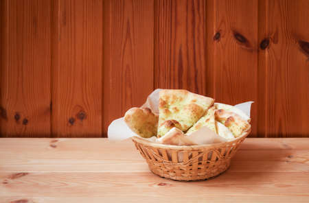 Wheat focaccia bread with pesto sauce in wicker basket on wooden table. Selective focus. View with copy space.
