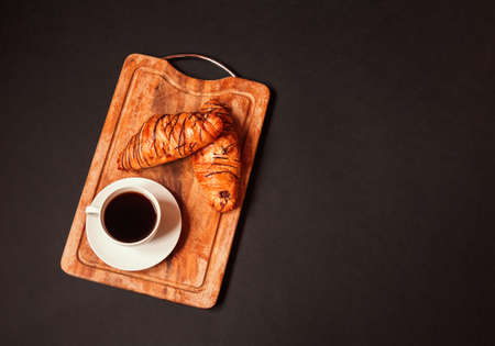 Cup of coffee and croissants on cutting board on dark background. Top view, copy space.