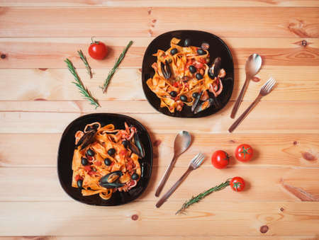 Two black plates of pappardelle pasta with seafood with tomato sauce on wooden table,  cherry tomatoes and rosemary near. Top view.