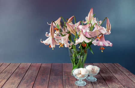 Bouquet of beige colored lilies with pink spots and bowls of ice cream on wooden table on gray background. View with copy space.