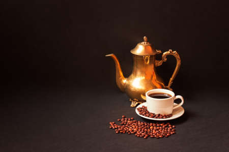 Coffee pot, coffee cup and coffee beans on dark background. View with copy space. Standard-Bild