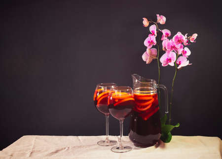 Red wine sangria with fruits in glasses and pitcher on  table. Purple orchid near. Dark background. View with copy space.