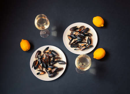 White plates with mussels and glasses of white wine on dark background. Top view.