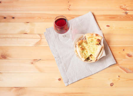 Glass of red wine and  wheat focaccia bread with aromatic pesto sauce on wooden table. Top view with copy space. Standard-Bild