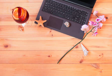 Laptop, glass of sangria, branch of orchid, starfish and seashells on wooden table. Summer holidays or freelance concept. Top view, copy space.