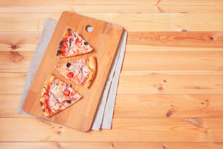 Pieces of delicious seafood pizza on cutting board on wooden table. Top view, copy space.