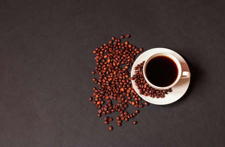 Cup of coffee and coffee beans on dark background. Top view with copy space.