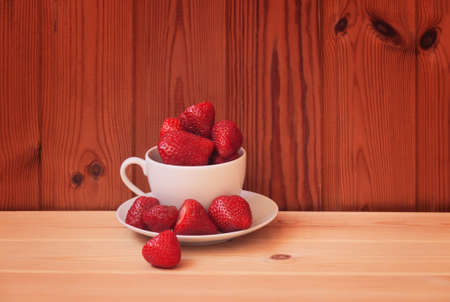 Fresh strawberries in white cup on wooden table. View with copy space. Standard-Bild