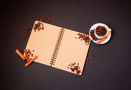 Empty notepad with coffee cup with roasted coffee beans and spices on dark background. Top view with copy space. Standard-Bild