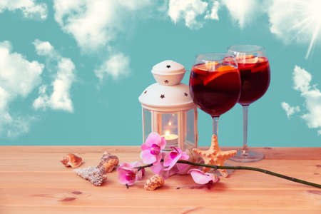 Red wine sangria with fruits in glasses, burning lantern, starfish, seashells and branch of orchid on wooden table. Summer holidays concept. Standard-Bild