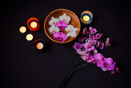 Orchids and candles on dark background. Top view, copy space.