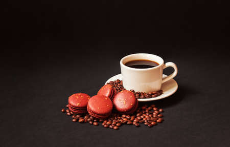 Coffee cup, chocolate macaroons and coffee beans on dark background.  View with copy space.