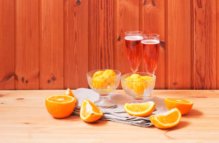 Glasses of rose champagne and bowls of orange sorbet ice cream on wooden table. View with copy space.