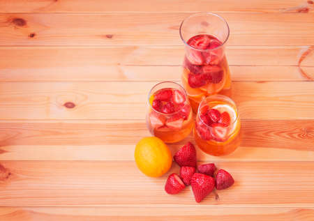Pitcher and glasses of summer lemonade with strawberries and lemon, strawberries and lemon  near on wooden table. Top view with copy space.