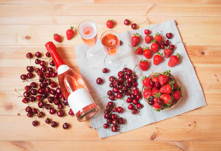 Bottle of rose champagne, glasses of rose champagne, fresh cherry and  strawberry on wooden table. Top view.
