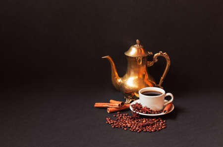 Coffee pot, coffee cup, spices and coffee beans on dark background. View with copy space.