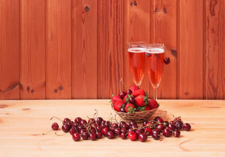Two glasses of rose champagne, fresh strawberry and cherry on wooden table. Selective focus. View with copy space.