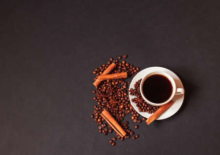 Cup of coffee, spices and coffee beans on dark background. Top view with copy space.