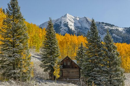 Little cabin surrounded by aspens and snow-covered peaks photo