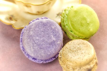 Three colorful macarons with teacup