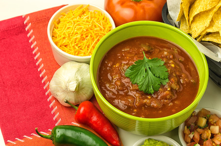 Green bowl of salsa with chips, cheese and other ingredients Imagens