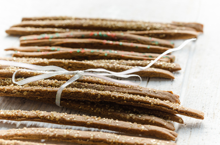 Glitter covered gingerbread sticks tied with a ribbon