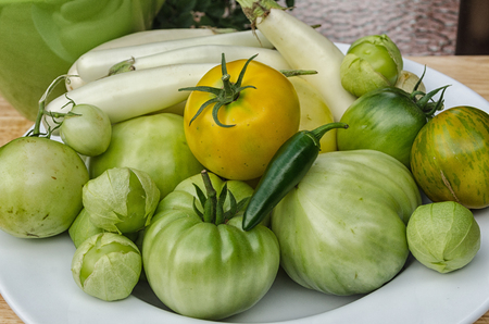 Assorted tomatoes, tomatillos and eggplant on a white plate