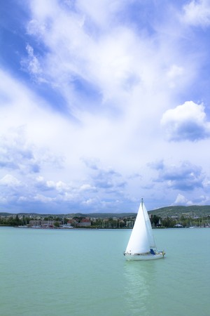 Sailing ship in the lake Balaton, under the blue sky, before the beach.