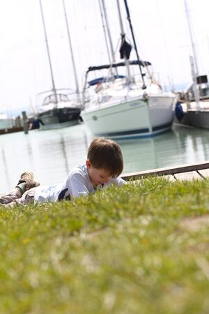 Young boy daydreaming in front of the lake Balaton and ships