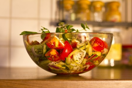 Salad of tomato, pepper, cucumber and purple onion, in olive oil, with menta and oregano sprig.