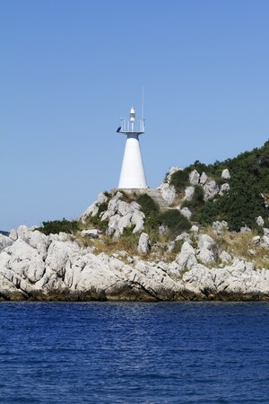 Bright white lighthouse on a small, rocky island photo