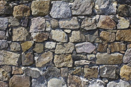stone wall in the broad daylight with different sized stones