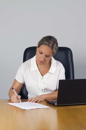 Professional businesswoman signing the papers in the office