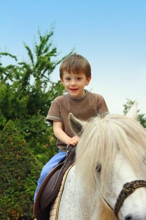 Lachende, jonge jongen rit een pony paard