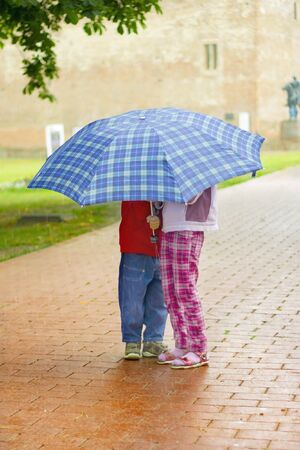 Young girl and boy under a blue umbrella in the rain