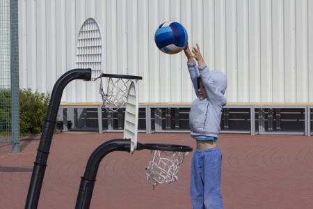 Adorable boy playing basketball outdoors, just drops the ball Stock Photo