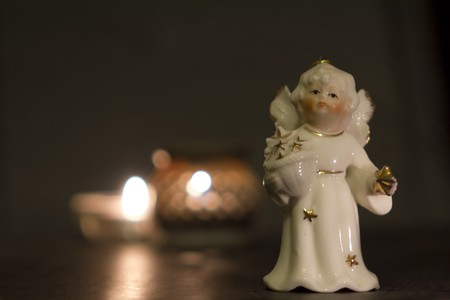White china christmas angel with golden stars and candles in the night   Stock Photo