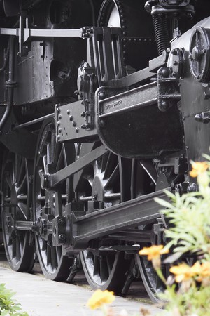Closeup of vintage steam engines black, iron wheel, with blurred flowers