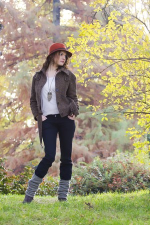 women in the autumn forest, in red hat, looking out  Stock Photo
