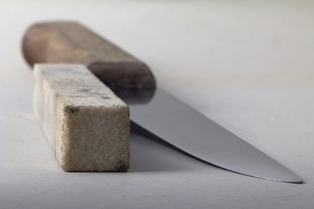honing: Kitchen knife and honing stone, shallow depth of field