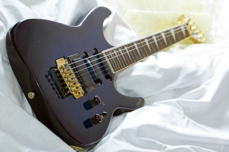 Blue metal guitar in the bed, selective focus