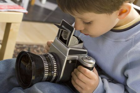 Young boy examining a vintage medium format camera Stock Photo