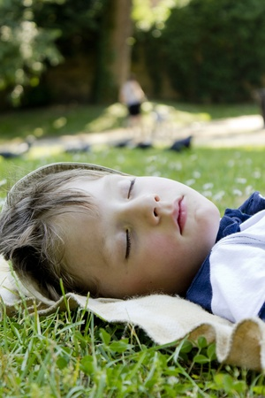 Young boy sleeping in the green grass.