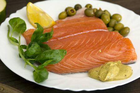 Nice, raw salmon filet, with lemon, mustard, basil and olives