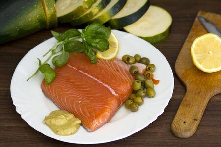 Nice, raw salmon filet, with lemon, mustard, basil and olives photo