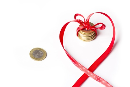 coins in a ribbon, contrast of money and feelings Stock Photo - 12116233