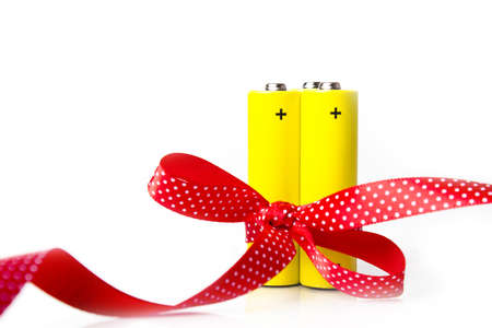 Yellow battery in ribbon. Isolated on white photo